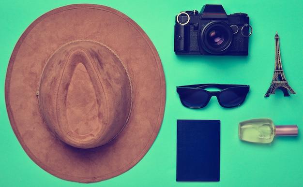 Поездка во францию, париж. фетровая шляпа, пленочная камера, солнцезащитные очки, паспорт, флакон духов, сувенирная статуэтка макета эйфелевой башни на синем фоне бумаги.