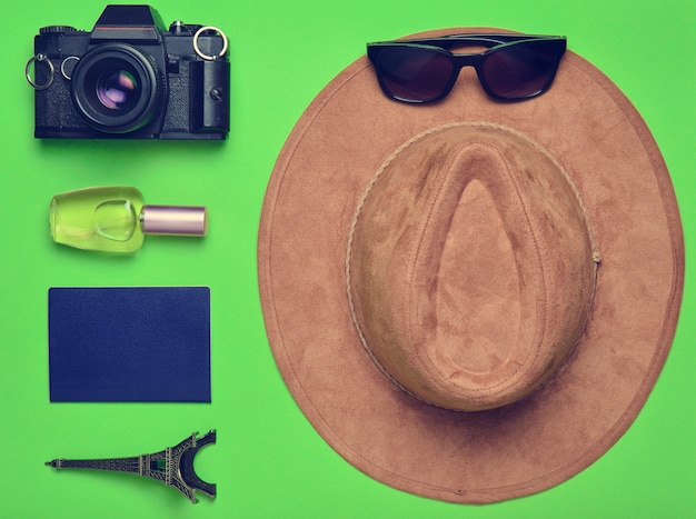 Поездка во францию, париж. фетровая шляпа, пленочная камера, солнцезащитные очки, паспорт, флакон духов, сувенирная статуэтка макета эйфелевой башни на фоне зеленой бумаги.