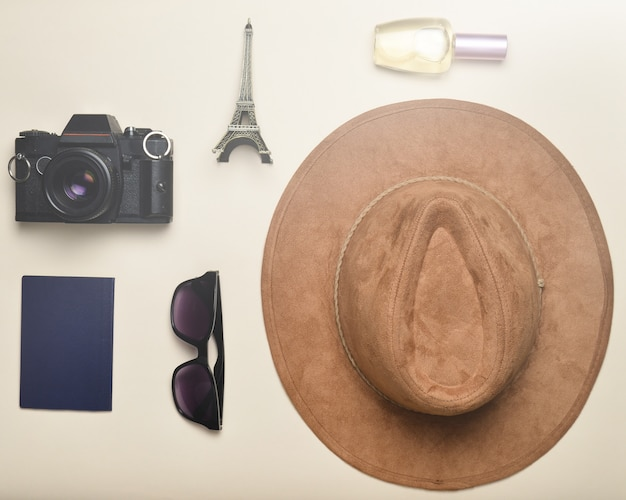 Поездка во францию, париж. фетровая шляпа, пленочная камера, солнцезащитные очки, паспорт, флакон духов, сувенирная статуэтка макета эйфелевой башни на фоне бумаги в пастельных тонах.