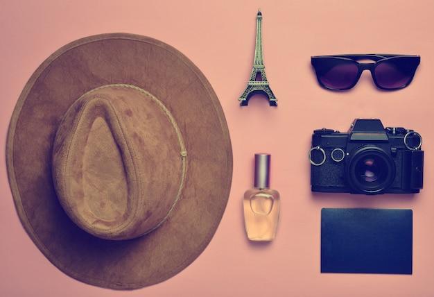 Поездка во францию, париж. фетровая шляпа, пленочная камера, солнцезащитные очки, паспорт, флакон духов, сувенирная статуэтка макета эйфелевой башни на розовом бумажном фоне.