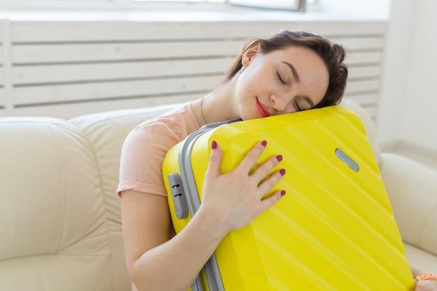 旅行旅行と休日のコンセプトの女性は旅行のために物を集めるのにうんざりしています