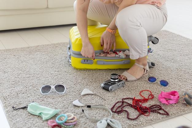 Концепция поездки, путешествий и праздников - женщина пытается закрыть свой чемодан