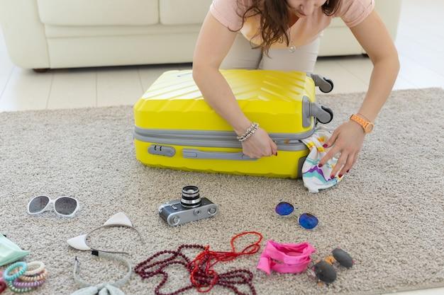 旅行、旅行、休日のコンセプト-スーツケースを閉じようとしている女性。