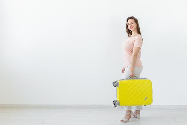 여행, 여행 및 휴일 개념-복사본과 흰색 배경 위에 그녀의 노란색 가방을 가진 여자