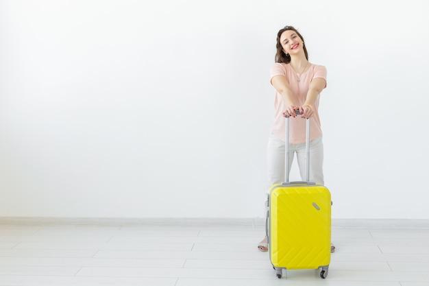 旅行、旅行、休日のコンセプト-コピースペースで白い表面に黄色のスーツケースを持つ女性