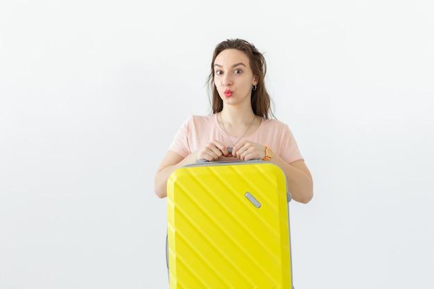 旅行、旅行、休日のコンセプト-白い表面に黄色のスーツケースを持つ女性
