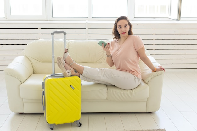 Trip, travel, and vacations concept - woman with yellow suitcase is waiting for the taxi