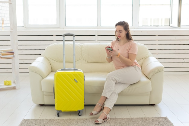 Trip travel and vacations concept  woman with yellow suitcase is waiting for the taxi