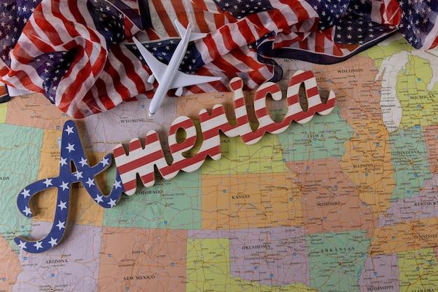 飛行機モデルの米国旅行のための旅行休暇の概念米国の地図上のアメリカの国旗