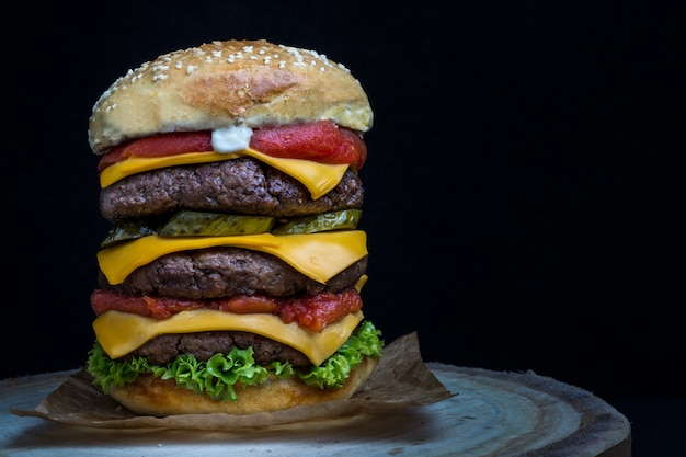 Triple cheeseburger with tomato, lettuce, pickles and mayonnaise