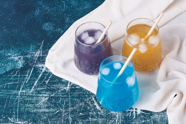 Triple color cups of drink on blue.