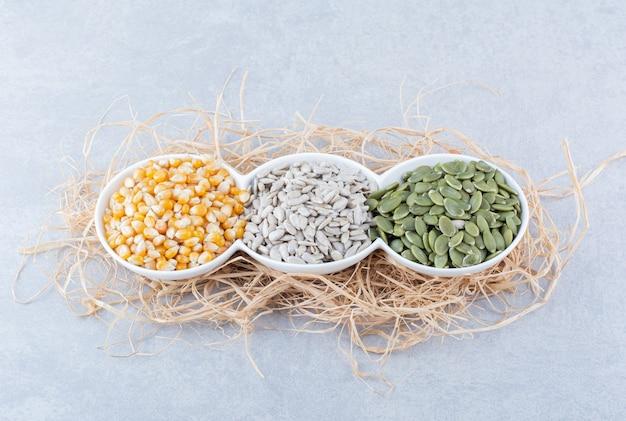 Triplo piatto rifornito con una piccola porzione di chicchi di mais, semi di girasole e pepitas su una pila di paglia su una superficie di marmo