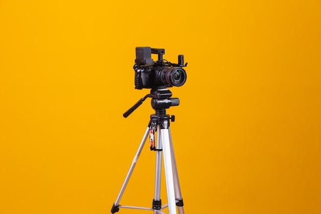 黄色の背景に三脚撮影カメラ