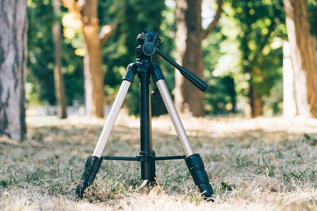 Tripod stands on the grass in the forest