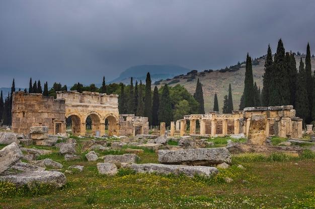 산의 배경에 터키 파묵칼레에있는 고대 도시 히 에라 폴리스의 개선문