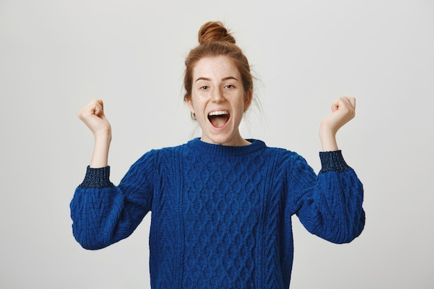 Triumphing cute redhead girl celebrate achievement, shouting yes