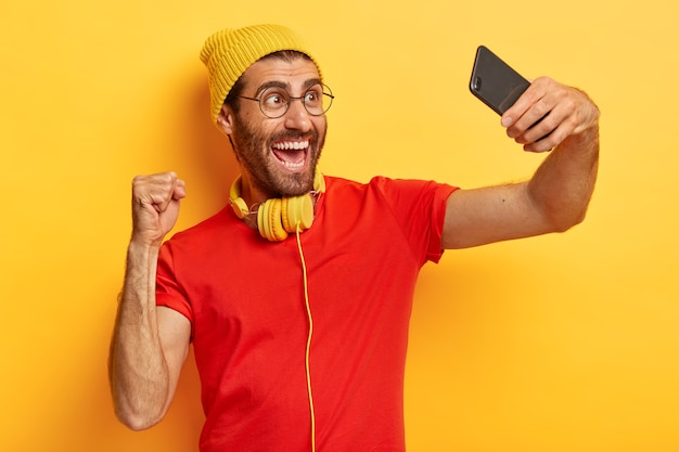 Triumphing glad man celebrates success, makes photo of himself, takes selfie, shoots video, wears hat, t shirt and spectacles isolated over yellow background. people