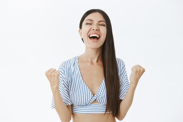 Торжествующая счастливая и обрадованная молодая успешная и удачливая женщина в укороченном топе кричит от радости