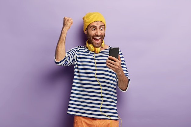 Triumphing happy guy raises clenched fist, celebrates winning lottery, gets message of confirming holds mobile phone, browses social media, wears yellow hat, striped jumper, always stays in touch