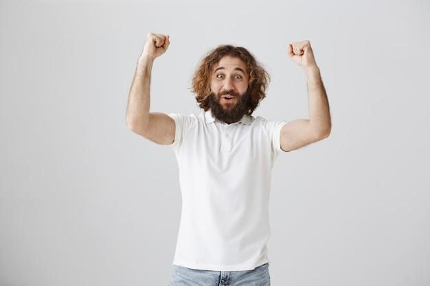 Торжествующий счастливый ближневосточный парень поднимает руки в жесте