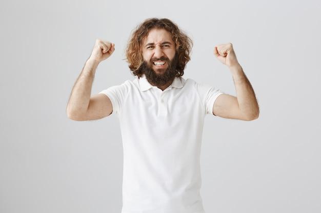 はいジェスチャーで手を上げて勝利を祝う幸せな中東の男を勝利に導く