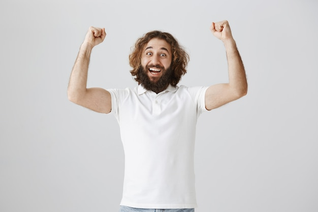 Triumphing happy middle-eastern guy raising hands in yes gesture, celebrating victory