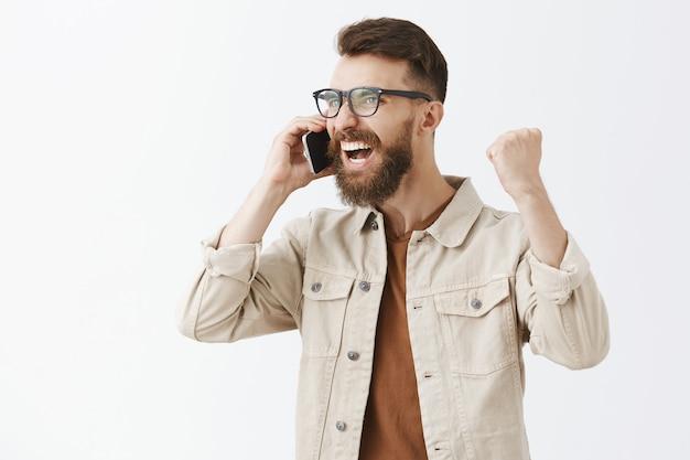 Uomo barbuto trionfante e gioioso con gli occhiali in posa contro il muro bianco
