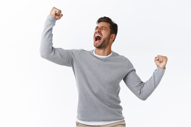 Triumphing young hispanic guy feeling like champion of world, celebrating success or win, yelling yes as finish competition, achieve victory or desirable, fist pump encouraged and motivated