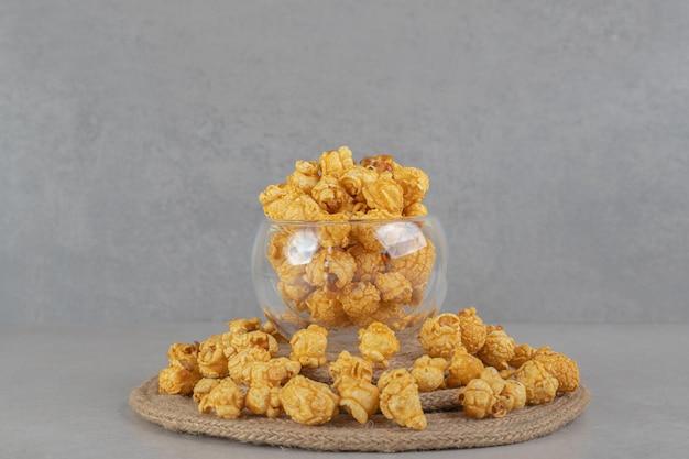 Sottopentola appoggiato sotto una ciotola di vetro piena inanellata con popcorn ricoperto di caramello su un tavolo di marmo.