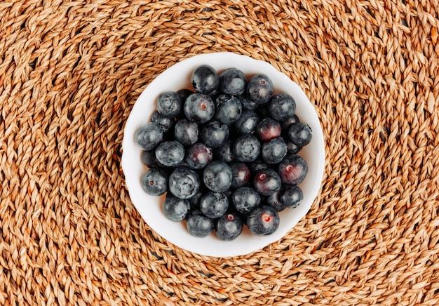 Черные оливки в миску на фоне ротанга trivet. вид сверху.