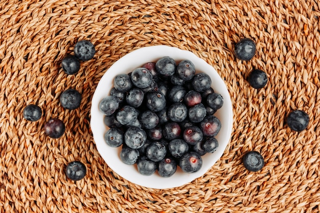 Некоторые черные оливки в шаре на предпосылке trivet ротанга, взгляд сверху.