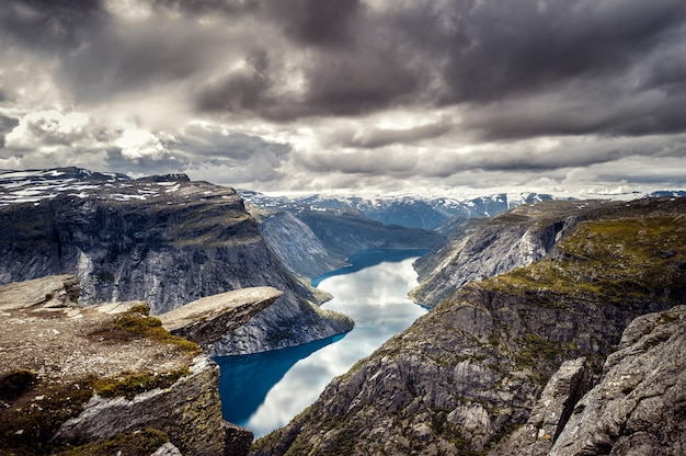 Язык тролля над фьордом в ущелье норвегии с облачным небом и заснеженными горными вершинами