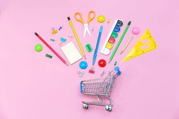 ピンクの背景に学用品とトロリーバナー。学校のコンセプトに戻ります。一年生のための文房具の購入