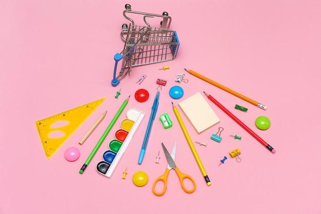 ピンクの背景に学用品が付いたトロリーバナーは、文房具を購入するための学校のコンセプトに戻ります...