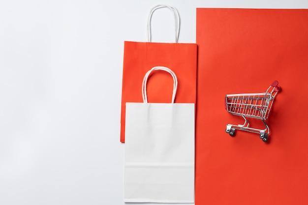 Тележка для супермаркета и упаковки на красном фоне