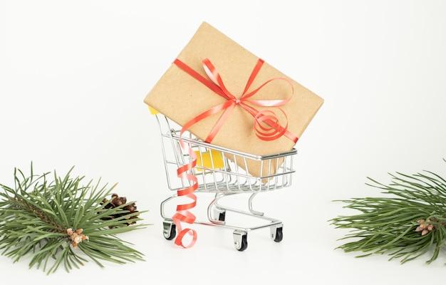 白い背景で隔離のクリスマスや誕生日のギフトボックスとスーパーマーケットのトロリーカート