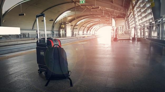 バックパック付きのトロリー荷物は駅の床に置かれています