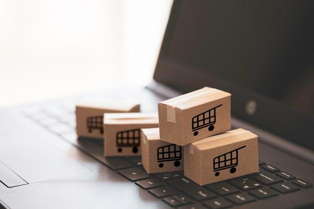 小さなカートンボックスのトロリーまたはショッピングカートのロゴは、キーボードコンピュータのラップトップに配置され、オンラインショッピングと顧客のコンセプトへのサービス提供を実現します。