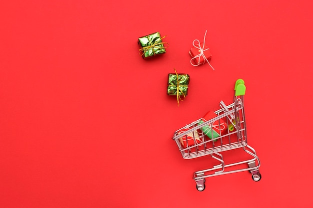 Trolley on a red bright background with gifts, top view.