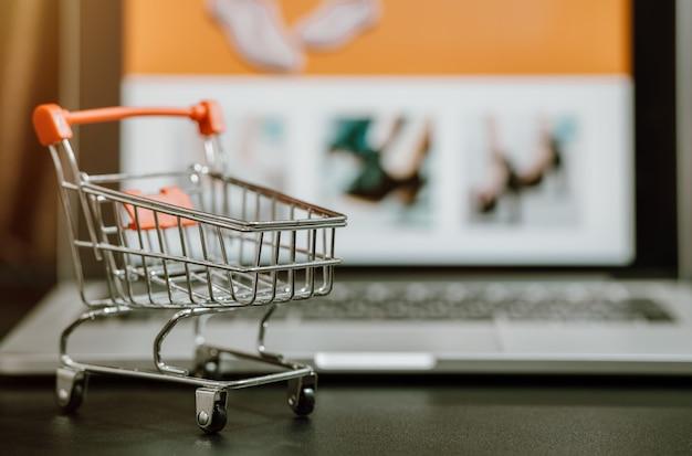 테이블에 컴퓨터 노트북과 트롤리 쇼핑 카트. 코로나 바이러스 covid-19 질병 예방을 위해 온라인 쇼핑 또는 인터넷에서 전자 상거래를위한 개념