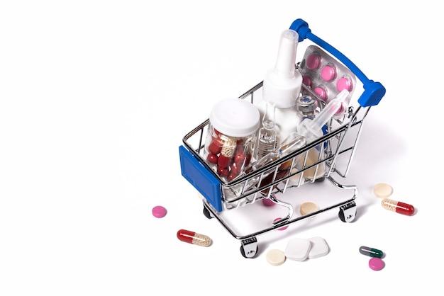 白い背景の上の薬とトロリー医療概念