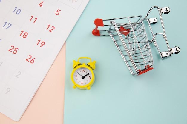 Тележка с желтым будильником, концепция покупок в интернете.
