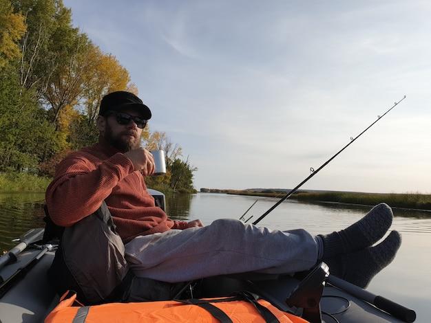 トローリング釣り、秋の晴れた日に川に浮かぶモーターボートに乗ったひげを生やした男、そして鉄のマグカップからお茶を飲む。