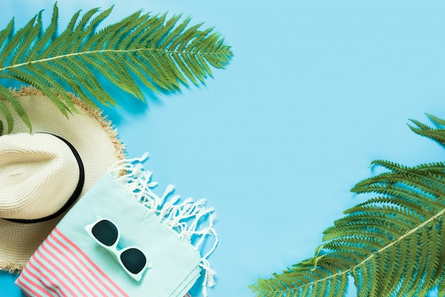 Tropacal vacation. straw beach sunhat, sun glasses, beach towel, leaf of fern on blue background.