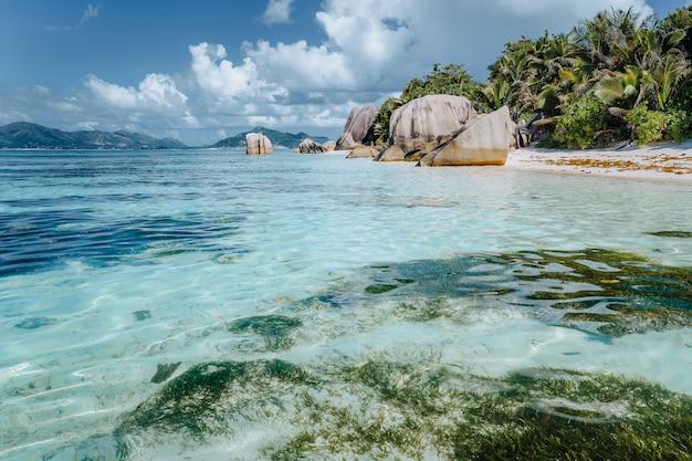 Тропический пляж anse source d'argent с неглубокой голубой лагуной и гранитными валунами