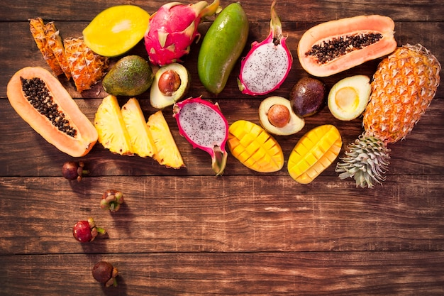 Tropical assorted fruits on a wooden background.