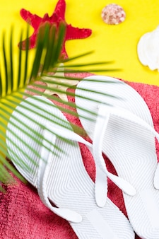 Tropical background palm trees branches with blurred set of woman's things accessories to beach season.
