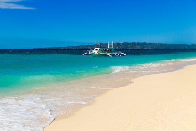 フィリピンのボラカイ島の熱帯のビーチとボートのある美しい海。背景に雲と青い空。