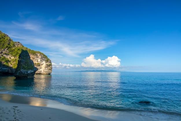 열대 해변과 관목으로 자란 절벽. 푸른 하늘과 수평선 위의 구름. 오후 그늘