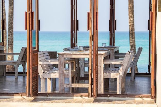 Тропическое пляжное кафе с деревянным столом и стульями с голубой морской водой на фоне, таиланд. деревянная мебель в деревенском стиле на балконе с видом на красивую равнину и бирюзовое море. концепция путешествия